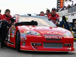 Tony Stewart's car is led onto the track before Monday's Daytona 500, which was postponed from Sunday because of rain.