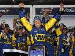 Next to a clock reading 12:48 a.m. (Tuesday), Matt Kenseth celebrates his second Daytona 500 win. He held off Dale Earnhardt Jr. at the finish line.