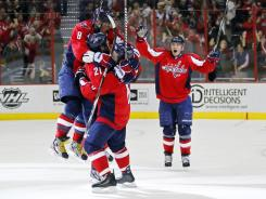 Washington's Troy Brouwer (20) celebrates with teammates after scoring the game-tying goal, his second in 3 1-2 minutes, at the end of regulation against the Islanders. The Capitals went on to win in overtime on an Alex Ovechkin goal.