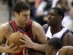 The New Jersey Nets' Brook Lopez, left, fights for a rebound against the Dallas Mavericks' Rodrigue Beaubois (3) and Ian Mahinmi.