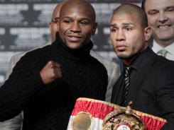 Floyd Mayweather, left, and Miguel Cotto, posing after a New York news conference on Tuesday, will fight for Cotto's 154-pound WBA title on May 5.