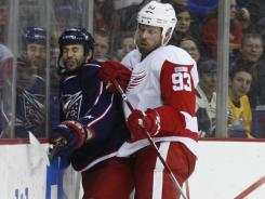 Red Wings forward Johan Franzen checks Derek MacKenzie of the Blue Jackets to get him off the puck during their game Tuesday. Franzen had a goal in the win.