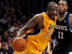 Wearing a mask to protect a broken nose, Kobe Bryant scored 31 points to lead the Lakers to a rout of the Timberwolves.
