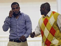 Former Denver Broncos cornerback Perrish Cox, left, talks on his phone as he walks the hallway with his uncle, Ron Davis, outside the courtroom in Castle Rock, Colo., on Thursday, March 1, 2012.