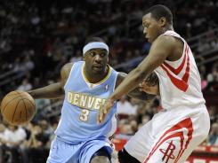 Denver's Ty Lawson pushes off Houston's Kyle Lowry to gain some seperation for a jump shot in the first half of their game on Friday. Lawson led the Nuggets to a victory.