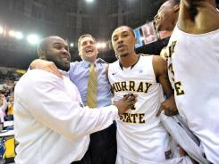 Murray State Racers head coach Steve Prohm celebrates with team members guards Donte Poole (11) and Isaiah Canaan (3) after defeating the Tennessee State Tigers 54-52.