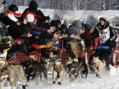 Kristy Berington greets fans as she and her team begins the Iditarod Trail Sled Dog Race.