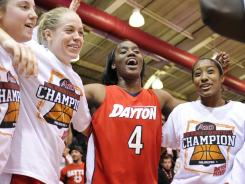 Dayton players, including forward Olivia Applewhite (4), celebrate after defeating the St. Bonaventure Bonnies in the finals of the A-10 Tournament at Hagan Arena in Philadelphia.