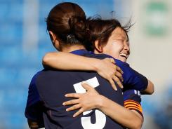 Japan's Aya Miyama (right) celebrates with teammate Aya Sameshima at the end of their Algarve Cup women's soccer match with the United States on Monday in Faro, Portugal. Japan defeated the USA 1-0.