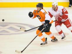 Flyers center Claude Giroux (28) picks up loose puck ahead of Detroit Red Wings defenseman Ian White (18) during second period of game at the Wells Fargo Center in Philadelphia. Giroux had a goal in the win.