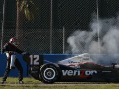 IndyCar driver Will Power sprays his car with a fire extinguisher after the engine caught fire during testing in Sebring, Fla.