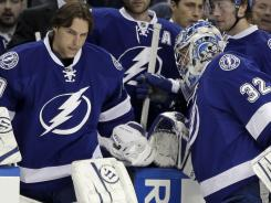 Tampa Bay Lightning goalie Dwayne Roloson, left, replaces Mathieu Garon after Garon was injured during the first period Tuesday.