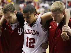 Hoosiers guard Verdell Jones III is helped off the floor by Kory Barneet (left) and Austin Etherington (right) after being injured.
