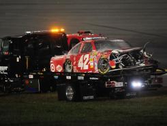 Juan Pablo Montoya's car is carried off the infield during the Daytona 500 on Feb. 27 after his spin-out slammed into a jet dryer under caution and sent it bursting into flames.