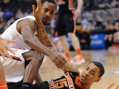 Oregon State forward Eric Moreland (15) and Arizona guard Kyle Fogg go for a loose ball in the second half of the first semi-final game in the Pac-12 Tournament at the Staples Center. Arizona won 72-61, advancing to the final.