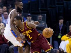 Cavaliers point guard Kyrie Irving (2) drives to the basket against Thunder guard James Harden during the first quarter on Friday. Irving led Cleveland to a win, giving Oklahoma City just their second home loss of the season.
