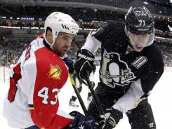 Penguins forward Evgeni Malkin (71) battles in the corner for the puck with the Panthers' Mike Weaver in the second period on Friday. Malkin's shootout goal gave Pittsburgh its eighth straight win.