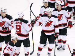 The Devils celebrate after their game against the Islanders after rallying late for a 2-1 victory.