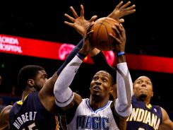 Magic center Dwight Howard, center, shoots between the Pacers' Roy Hibbert (55) and David West during the first quarter Sunday at Amway Center. Howard had 30 points and 13 rebounds in Orlando's victory.
