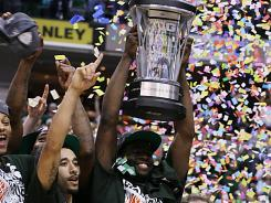 Michigan State forward Draymond Green holds up the trophy with Spartans teammates and head coach Tom Izzo after they won the Big Ten tournament title over Ohio State.