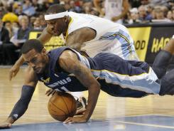 Grizzlies guard Mike Conley, front, beats Nuggets guard Ty Lawson to a loose ball during the first quarter of their game on Sunday. Conley had 13 points and seven assists as Memphis won in Denver.