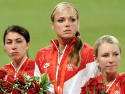 Andrea Duran (left), Jennie Finch and Caitlin Lowe watch Japanese players receive their gold medals during the medal ceremony after Japan defeated the United States 3-1 to win the gold medal during the 2008 Beijing Olympics