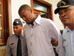 Fausto Carmona, whose real name is Roberto Hernandez Heredia, center, is escorted by police out of court in Santo Domingo, Dominican Republic.