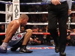 Juan Manuel Lopez tries to get up after being knocked down in the 10th round by Orlando Salido Saturday night, as referee Roberto Ramirez directs Salido to the opposite corner. Ramirez stopped the fight at that point.