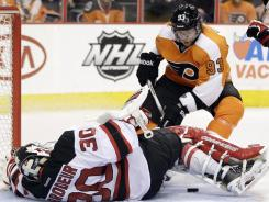 Despite being on his back, Devils goalie Martin Brodeur manages to block a shot by Flyers forward Jakub Voracek on Tuesday.