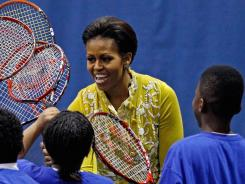 First Lady Michelle Obama gives racket high-fives to MacFarland Middle School students during an Olympics-themed event Tuesday at American University in Washington, D.C.