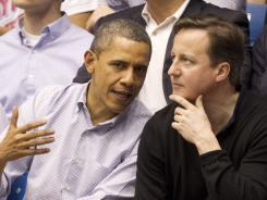 United States president Barack Obama talks with British Prime Minister David Cameron before the game between the Western Kentucky and Mississippi Valley State.