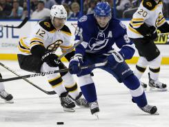Tampa Bay's Steven Stamkos works the puck past Boston's Brian Rolston on his way to the net on Tuesday. Stamkos had two goals, giving him 50 for the season.