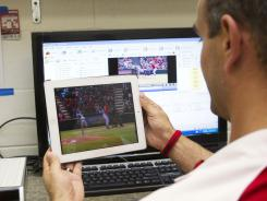 Angels senior video coordinator Diego Lopez looks at video of the Angels players on an iPad.