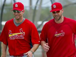 Cardinals pitchers Adam Wainwright, left, and Chris Carpenter jog to their next station during a spring workout.