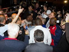British heavyweight boxer Dereck Chisora, center in light shirt, is surrounded by media and others, following his brawl with former WBA champion David Haye at a post-fight press conference on Feb. 19, 2012.
