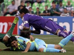 Fredy Montero of the Seattle Sounders, bottom, grimaces as Osvaldo Sanchez, goalkeeper of Mexico's Santos Laguna team, dives for the ball during a CONCACAF Champions League quarterfinal soccer game in Torreon, Mexico, on Wednesday.