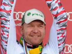Klaus Kroell poses on the podium after winning the men's Alpine skiing World Cup downhill title in Schladming, Austria on March 14.