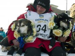 Dallas Seavey holds his leaders, Diesel, left, and Guiness after he arrived at the finish line to claim victory in the Iditarod Trail Sled Dog Race in Nome, Alaska, on Tuesday. Seavey is the youngest musher to win the nearly 1,000-mile race across Alaska.