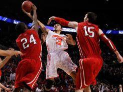 Louisville's Peyton Siva (3) tries to shoot between Davidson's De'Mon Brooks (24) and Jake Cohen. Siva had a large fan contingent at the game in Portland.