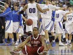Alabama's Trevor Releford sits on the court as Creighton players celebrate at the end of the Bluejays' win.