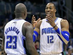 Orlando Magic's Dwight Howard (12) laughs with teammate Jason Richardson (23) against the New Jersey Nets, Friday, March 16, 2012 in Orlando, Fla. Orlando won 86-70.