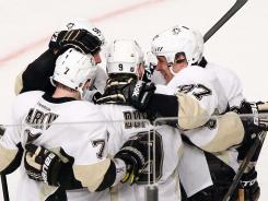 Pittsburgh Penguins players celebrate Pascal Dupuis' goal Thursday night. Sidney Crosby was given an assist on the goal.