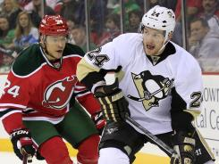 Pittsburgh Penguins winger Matt Cooke, right, handles the puck as New Jersey Devils defenseman Bryce Salvador chases on Saturday. Cooke had two goals.