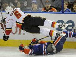 Calgary Flames defenseman Cory Sarich, top, crashes into the Edmonton Oilers' Taylor Hall during the first period Friday.