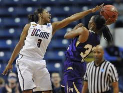 Connecticut's Tiffany Hayes stifles Prairie View A&M's Kiara Etienne during their first-round NCAA playoff game. The No. 1 Huskies won by 36 points.
