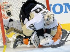 Philadelphia's Matt Read slides into Pittsburgh goalie Marc-Andre Fleury during the first period Sunday.