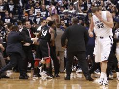Xavier center Kenny Frease, who had been punched in the eye, walks away from the brawl that broke out Dec. 10 in the final seconds of the annual showdown with Cincinnati.
