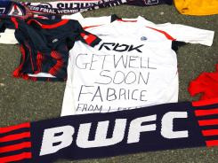 Tributes and get well messages are laid outside the Reebok Stadium on Monday in Bolton, England for Bolton Wanderers' Fabrice Muamba.