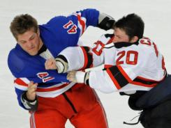 New Jersey's Ryan Carter, right, fights with New York's Stu Bickel off the opening faceoff.