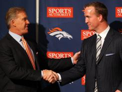 Peyton Manning shakes hands with executive vice president of football operations John Elway during a news conference announcing the former's contract with the Denver Broncos.